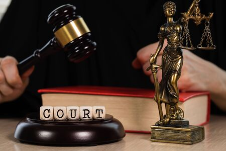 Word  COURT composed of wooden dices. Wooden gavel and statue of Themis in the background. Closeup Stock Photo