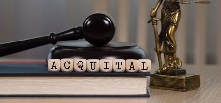 Word ACQUITAL composed of wooden dices. Wooden gavel and statue of Themis in the background. Closeup