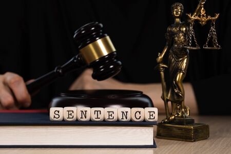 Word SENTENCE composed of wooden dices.  Wooden gavel and statue of Themis in the background. Closeup