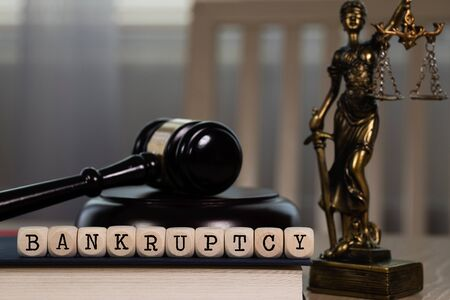 Word BANKRUPTCY composed of wooden dices. Wooden gavel and statue of Themis in the background. Closeup