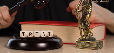 Word TRIAL composed of wooden dices.  Wooden gavel and statue of Themis in the background. Closeup