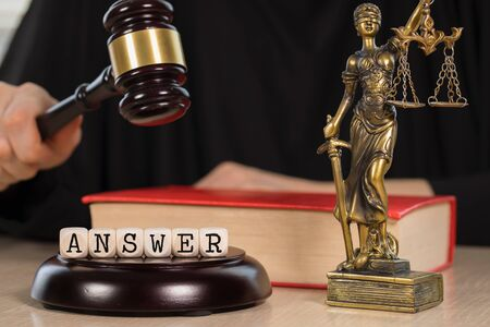 Word ANSWER composed of wooden dices. Wooden gavel and statue of Themis in the background. Closeup 写真素材