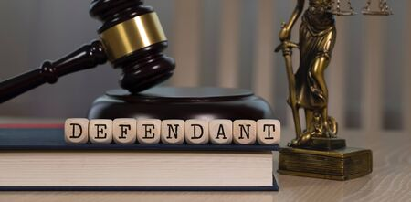 Word DEFENDANT composed of wooden dices.  Wooden gavel and statue of Themis in the background. Closeup 写真素材
