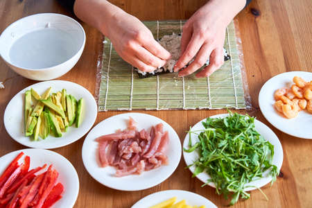 young woman prepares sushi with fresh ingredients at home. on wooden table.