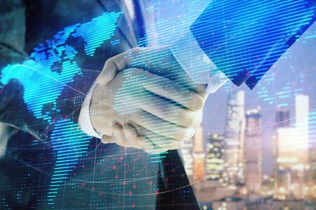 Double exposure of world map on cityscape background with two businessmen handshake. Concept of international business 写真素材