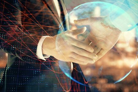 Double exposure of world map on cityscape background with two businessmen handshake. Concept of international business Imagens