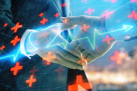 Double exposure of heart drawing on city view background with handshake. Concept of medical education