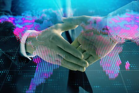 Multi exposure of world map on abstract background with two businessmen handshake. Concept of international business 写真素材