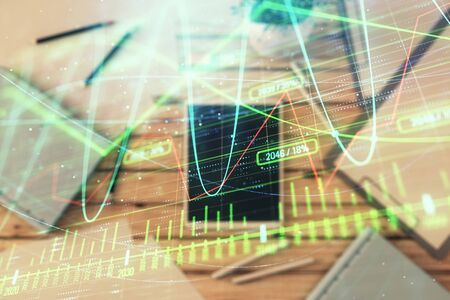 Double exposure of forex graph on digital tablet laying on table background. Concept of market analysis 写真素材