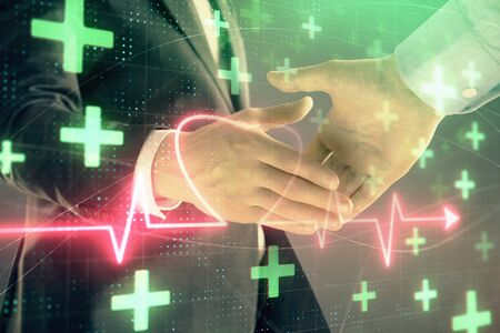 Multi exposure of heart hologram on abstract background with two men handshake. Concept of medical education Stock fotó