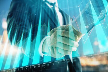 Double exposure of financial chart on cityscape background with two businessmen handshake. Concept of financial analysis and investment opportunities 版權商用圖片 - 129864327