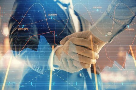 Double exposure of financial chart on cityscape background with two businessmen handshake. Concept of financial analysis and investment opportunities 版權商用圖片 - 129864328