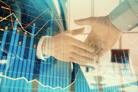 Multi exposure of financial graph on office background with two businessmen handshake. Concept of success in business 版權商用圖片 - 129864344