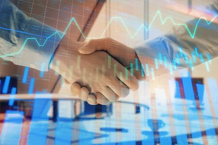 Multi exposure of financial graph on office background with two businessmen handshake. Concept of success in business 版權商用圖片