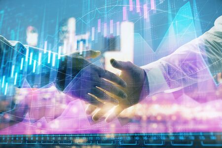 Double exposure of financial chart on cityscape background with two businessmen handshake. Concept of financial analysis and investment opportunities Stok Fotoğraf - 129831567