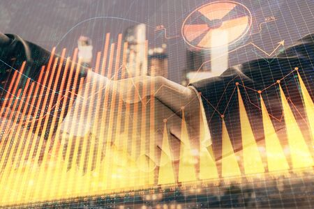 Double exposure of financial graph on cityscape background with two businessman handshake. Concept of stock market deal Фото со стока - 129831409