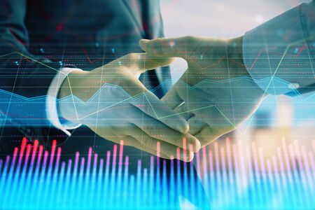 Double exposure of financial graph on cityscape background with two businessman handshake. Concept of stock market deal Фото со стока - 129831420