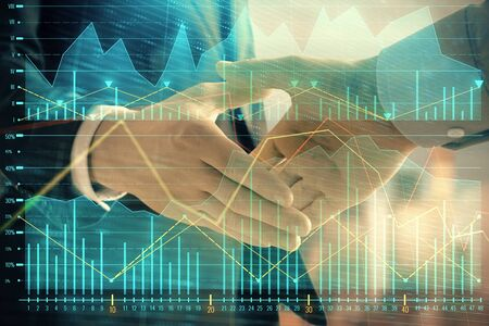Double exposure of financial graph on cityscape background with two businessman handshake. Concept of stock market deal Фото со стока - 129831421
