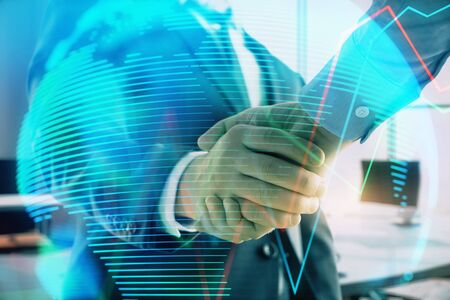 Multi exposure of financial chart and map on office background with two businessmen handshake. Concept of success in business