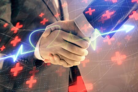 Multi exposure of heart hologram on abstract background with two men handshake. Concept of medical education