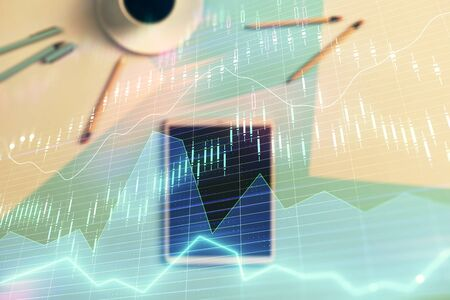 Double exposure of forex graph on digital tablet laying on table background. Concept of market analysis Фото со стока