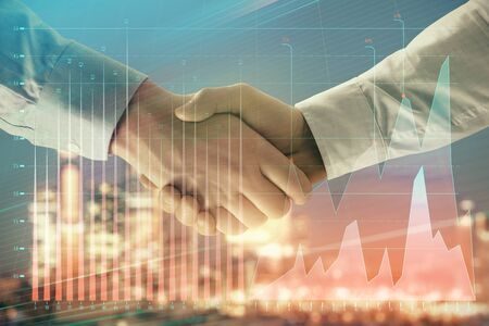Double exposure of financial chart on cityscape background with two businessmen handshake. Concept of financial analysis and investment opportunities Фото со стока - 129830423