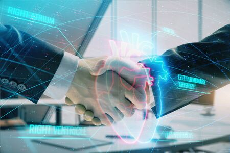Multi exposure of heart icon hologram on office background with two men handshake. Concept of medical education