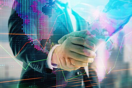 Double exposure of financial chart and world map on cityscape background with two businessmen handshake. Concept of international investment Stock Photo - 130140625