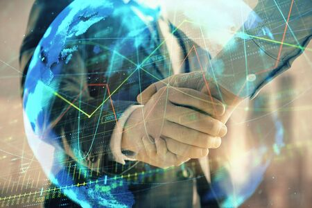 Double exposure of financial chart and world map on cityscape background with two businessmen handshake. Concept of international investment Stock Photo - 130141518
