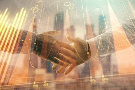 Double exposure of financial graph on cityscape background with two businessman handshake. Concept of stock market deal Stock Photo - 130141520