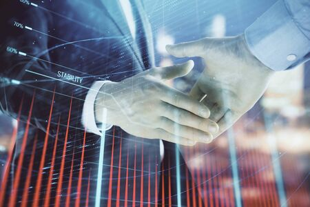 Double exposure of financial chart on cityscape background with two businessmen handshake. Concept of financial analysis and investment opportunities Stock Photo - 130141607