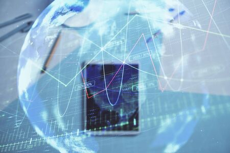 Double exposure of forex chart and world map on digital tablet laying on table background. Concept of market analysis Stok Fotoğraf