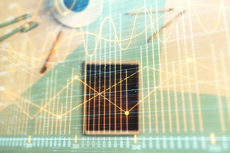 Double exposure of forex graph on digital tablet laying on table background. Concept of market analysis Reklamní fotografie