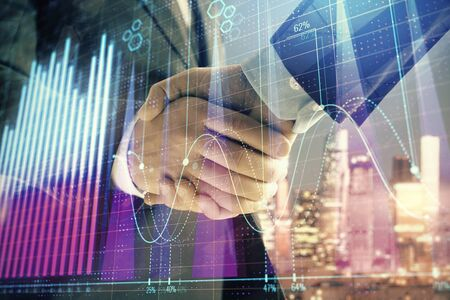 Double exposure of financial chart on cityscape background with two businessmen handshake. Concept of financial analysis and investment opportunities Stock Photo - 130163039