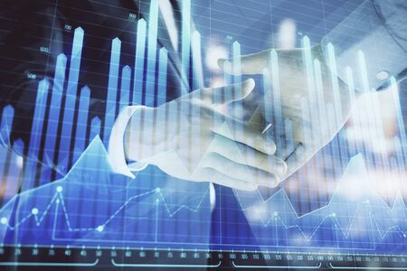 Double exposure of financial chart on cityscape background with two businessmen handshake. Concept of financial analysis and investment opportunities Stock fotó - 130163042