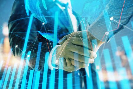 Double exposure of financial chart and world map on cityscape background with two businessmen handshake. Concept of international investment Stock fotó - 130163052