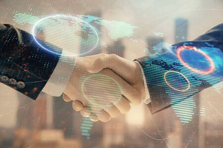 Double exposure of world map on cityscape background with two businessmen handshake. Concept of international business Stockfoto