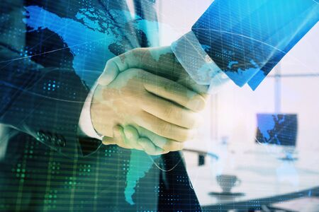 Multi exposure of world map on office background with two businessmen handshake. Concept of international business Stock Photo