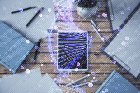 Double exposure of DNA hologram on digital tablet, table background. Concept of education Stock Photo