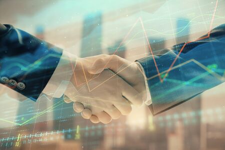 Double exposure of financial graph on cityscape background with two businessman handshake. Concept of stock market deal