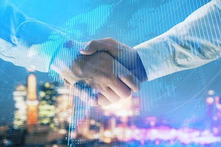 Double exposure of world map on cityscape background with two businessmen handshake. Concept of international business
