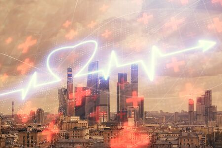 Multi exposure of human heart hologram on Moscow cityscape background. Concept of medical education