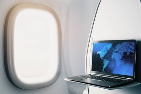 Laptop closeup inside airplane with world map on screen. International market trading concept. 3d rendering.