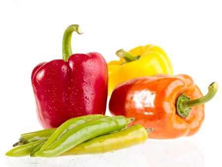 focused: peppers on white wet background. Focused on front green peppers