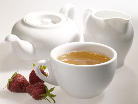 dishware: cup of black tea on the table with dishware and strawberry