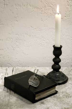 Holy Bible on the desk with burning candle photo