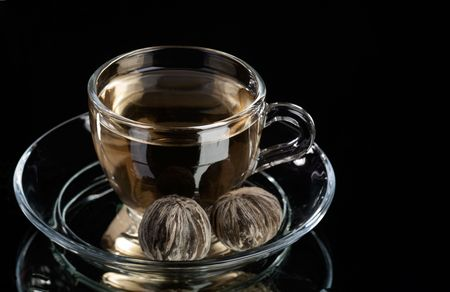 Cup of pure green tea over abstract black background photo