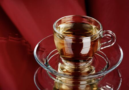Cup of pure green tea over abstract red background photo