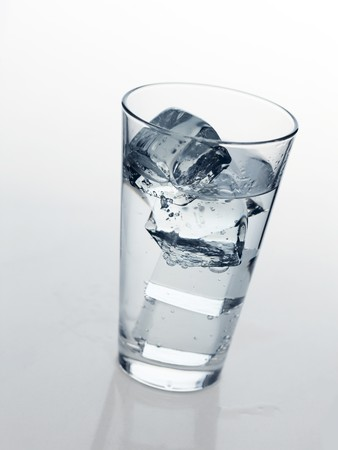 glass with cold mineral water, bubbles and ice photo