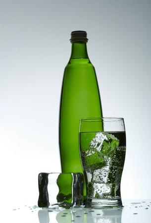 purified: Agua purificada fr�a en el cristal con burbujas y la reflexi�n sobre el fondo mojado